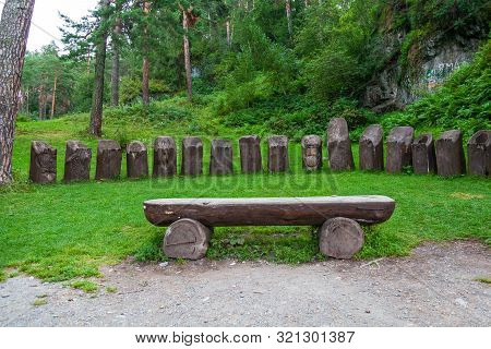 A Large Wooden Bench Made Of Half A Tree Trunk On A Green Grass Lawn In A Park
