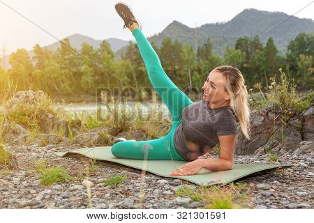 Blond Pretty Woman Smiling And Doing Stretching By Lifting One Leg Up And To The Side Against The Cl