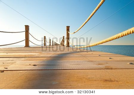 close up view of tropical wooden pier at sunny weather, clear skies