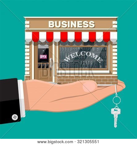 Hand Holding Shop Or Commercial Property With Key. Real Estate Business Promotional, Startup. Sellin