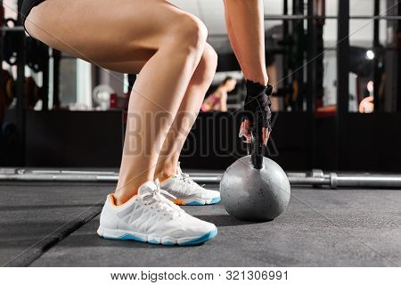 Athletic Woman Wearing Pink And Black Professional Sportswear Exercising With A Kettlebell At The Gy