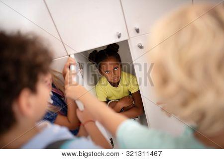 Dark-skinned Girl Suffering From Mockery And Sitting In Locker