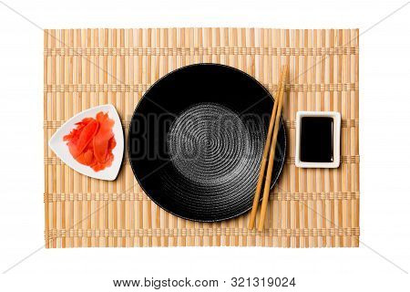 Empty Round Black Plate With Chopsticks For Sushi And Soy Sauce, Ginger On Yellow Bamboo Mat Backgro