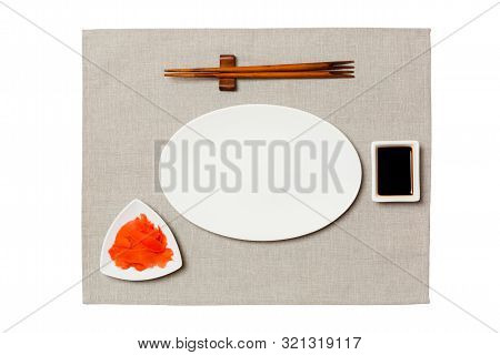 Empty Oval White Plate With Chopsticks For Sushi, Ginger And Soy Sauce On Grey Napkin Background. To