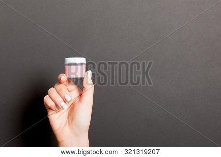 Female Hand Holding Cream Bottle Of Lotion Isolated. Girl Give Jar Cosmetic Products On Black Backgr