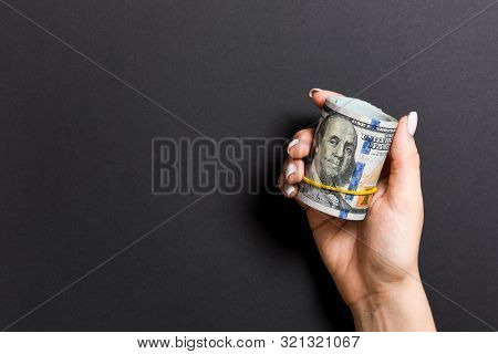 Top View Of Female Hand Holding A Pack Of Rolled Money On Colorful Background. One Hundred Dollars.