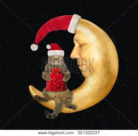 The Cat With A Sack Of Christmas Gifts Sits On The Moon Wearing A Santa Claus Hat. Stars Background.