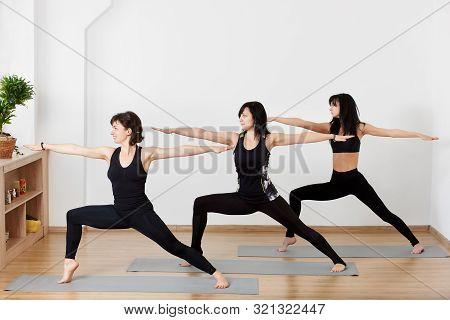 Beautiful Sporty Fit Women Practicing Ashtanga Vinyasa Yoga Asana Virabhadrasana 2 Pose. Group Of Fe