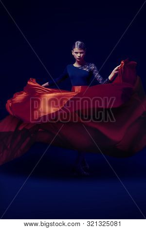Beautiful girl professional dancer performs latino dance. Passion and expression. Black background. poster