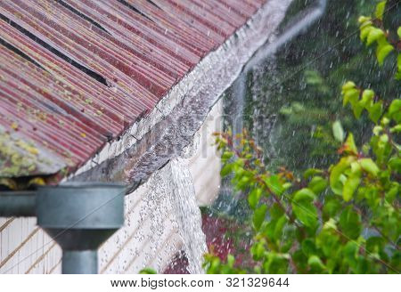 Water Overflowing From Damaged Rain Gutter During A Heavy Rainstorm