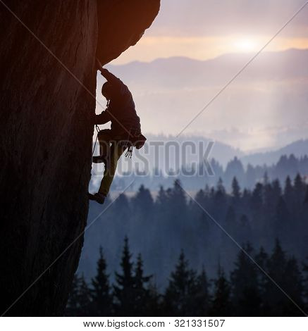 Silhouette Of Man Rock Climbing On Straight Vertical Rock At Sunrise. Sunlight Covering Mountains On
