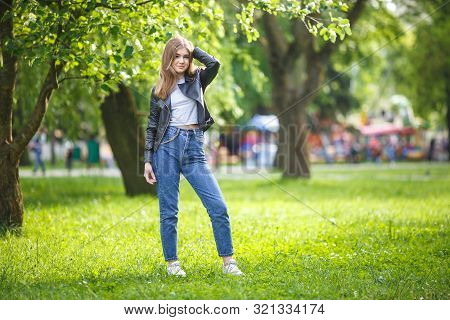 Portrait Of Little Beautiful Stylish Kid Girl With Bag In City Park On Green Forest Background