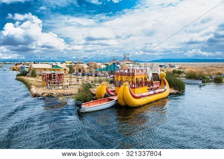 Uros, Peru - Jan 5, 2019. Traditional Totora boat with tourists on Titicaca lake near to the Uros floating islands , Puno, Peru, South America.