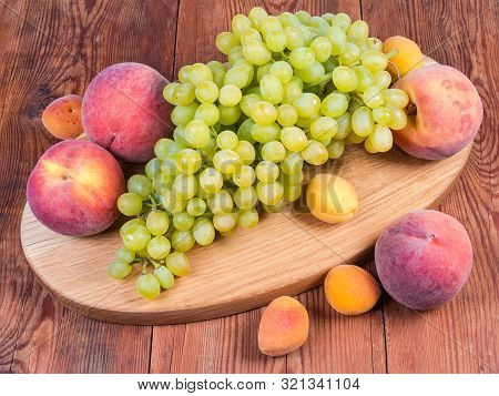 Cluster Of The Ripe White Seedless Grapes, Several Fresh Peaches And Apricots On The Oval Wooden Ser