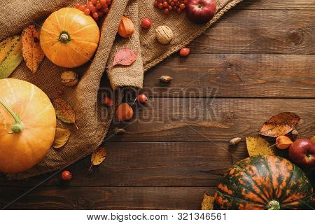 Autumn Frame Made Of Pumpkins, Dried Fall Leaves, Apples, Red Berries, Walnuts, Blanket On Wooden Ta