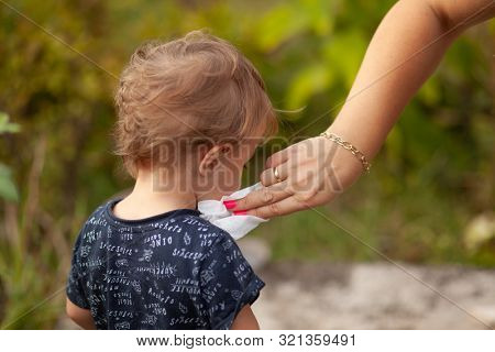 Hygiene - mom wiping the baby face skin with wet wipes. Cleaning wipe, pure, clean, outdoor