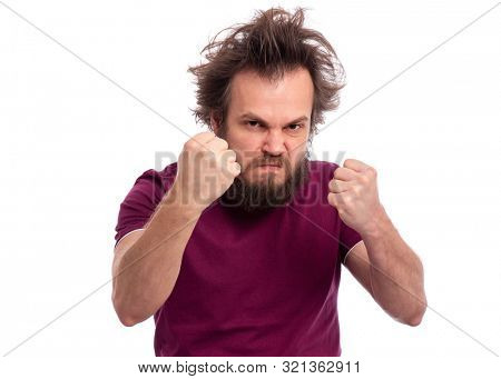 Portrait of adult bearded man showing fist with angry expression, isolated on white background. Crazy male showing fist. Upset and mad caucasian man with funny haircut in rage looking furious.
