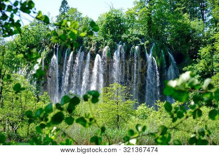 Veliki Prstavac Waterfall Framed By Green Leaves And Branches, At Plitvice Lakes (plitvicka Jezera),