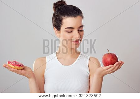 Woman Making Choice Between Apple And Donut. Dieting Concept. Brunette Girl Holds A Pink Donut And A