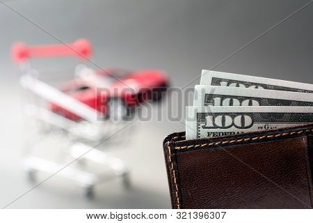 Leather Wallet With Dollars Blurred Red Car Shopping Trolley On The Background. Cheap Used Cars Conc
