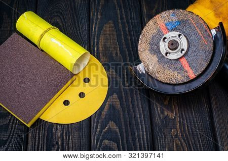 Set of abrasive tools and sandpaper on dark vintage wood background. The wizard is used for grinding items poster