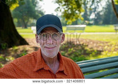 A Senior Man In Blue Baseball Cap And Orange Shirt, Portrait