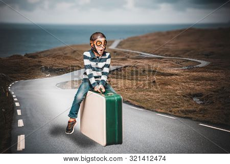 child dressed as an airman on a suitcase imagines to live an adventure flying on a lost road poster