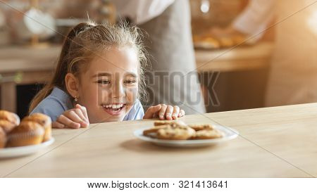 Kids And Sweets Concept. Adorable Little Girl Craving Cookies, Looking At Sweets In Kitchen, Panoram