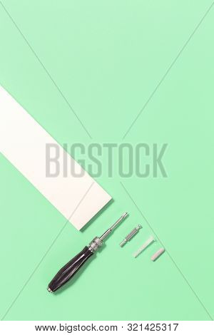 Tools For Assembly Of Flat Packed Furniture On Green Mint Background. White Diy Funiture Parts With