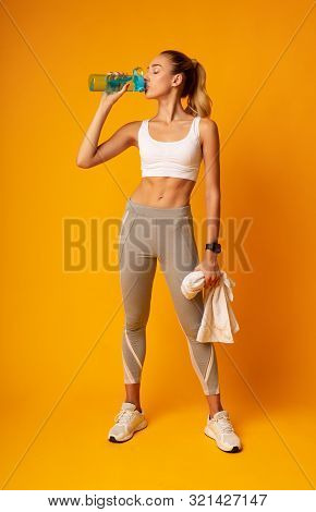 Slim Young Lady Drinking Water Holding Towel Standing Over Yellow Background In Studio. Workout Brea