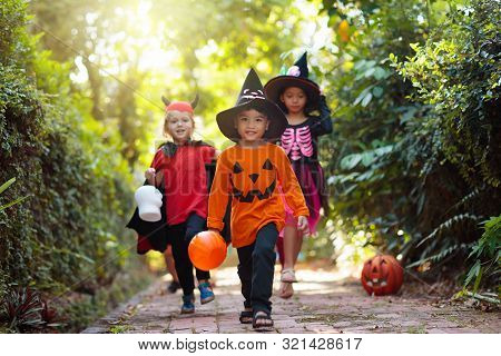 Kids Trick Or Treat On Halloween Night. Child At Decorated House Door With Autumn Leaf Wreath And Pu
