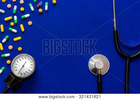 Medical Pills, Tonometer And Stethoscope On The Blue Surface. Blood Pressure Measurement. Color Caps