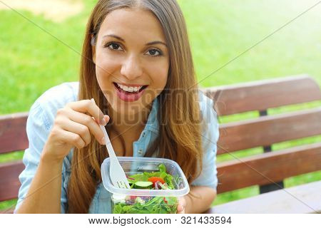 Happy Smiling Woman Eating Salad Sitting In The Park Looks At Camera With Copy Space Area. Lunch Sal