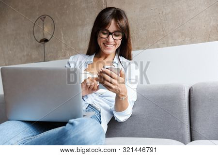 Image of a young happy business woman indoors at home on sofa in living room using laptop computer using mobile phone.