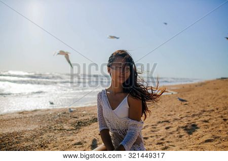 Woman Meditating At The Sea With Flying Seagulls