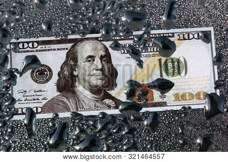 Paper dollar lies in a puddle of oil