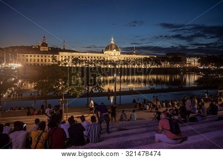 Lyon, France - July 18, 2019: French People Sitting On The Riverbank Of The Quais De Rhone, Facing H