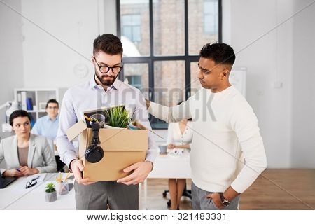 business, firing and job loss concept - colleague seeing off sad fired male office worker holding box of his personal stuff