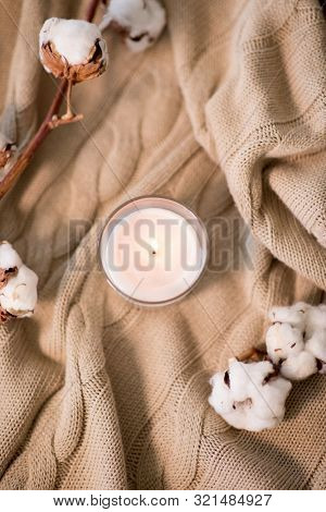 decoration, hygge and cosiness concept - burning wite fragrance candle and cotton flower on knitted blanket
