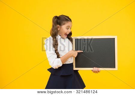 A Good Publicity For Our School. Small Kid Pointing Finger At Blank Blackboard With School Publicity