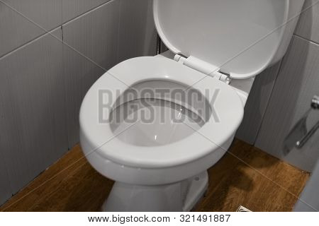 White Toilet Bowl In A Bathroom. Closeup View Of A Flushing White Toilet. The Water Swirls In The To