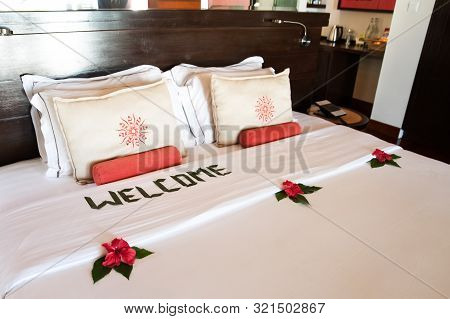 Large Bed With White Pillows And A Coverlet, Decorated With Tropical Flowers And An Inscription - We