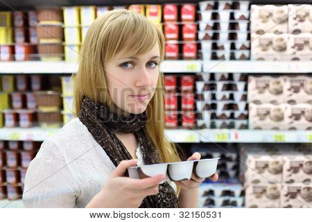 Blonde girl wearing scarf chooses yoghurt in store; shallow depth of field poster