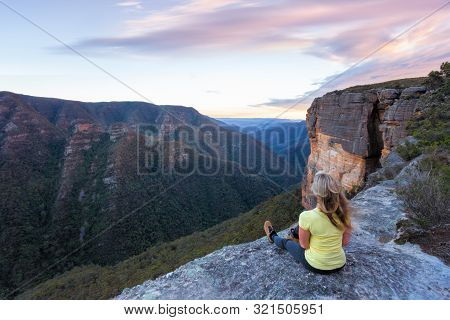 Woman With Long Blonde Wind Swept Hair Sitting On The Edge Of The Mountain Cliffs Looking Out Over T