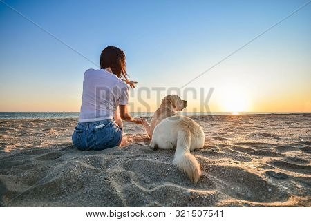 Friendship Concept With Woman And Dog Sitting Together On A Beach And Enjoying Sunset