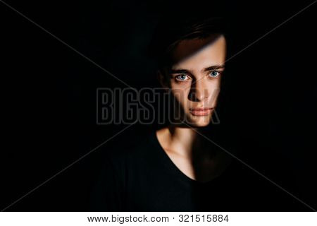 A portrait of a young goodlooking guy in a black t-shirt. Beauty of men, casual fashion.