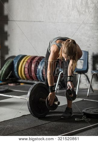 Female weight lifter loading weights onto barbell in gym.