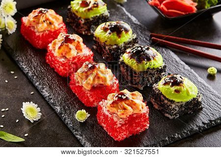 Spicy roll with masago caviar and wasabi. Sushi bar dish, restaurant menu item. Traditional eastern cuisine, national japanese cooking. Delicious asian snack, appetizer on wooden platter closeup