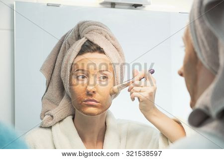 Young Woman Puts Clay Mask On Her Face With Brush Looking In Mirror In Bathroom. The Concept Of Self