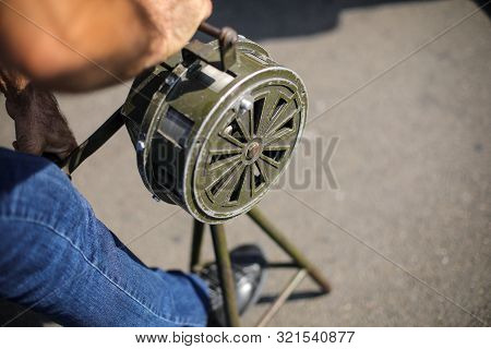 Shallow Depth Of Field Image With A Man Handling A Vintage Hand Crank Air Raid Siren